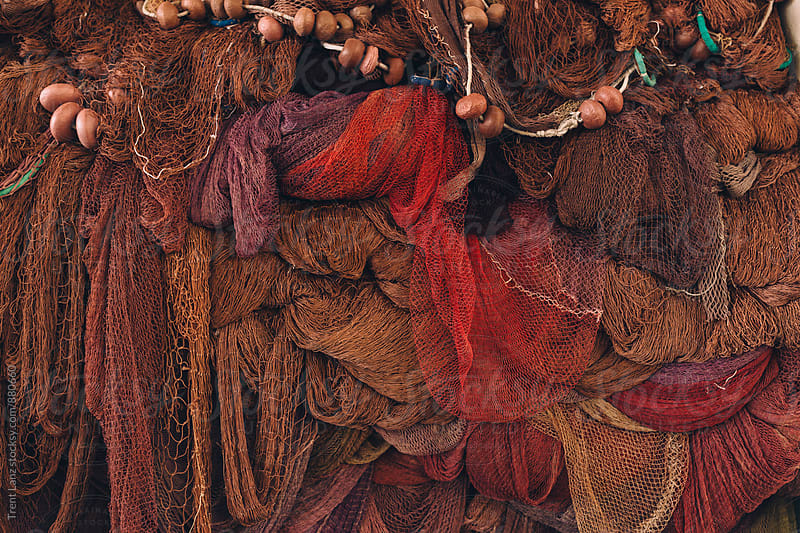 Colorful fish nets hanging in a big pile in Italian fishing village by Trent Lanz for Stocksy United