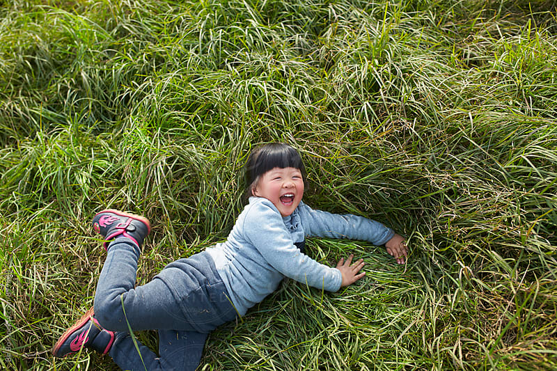 happy litte asian girl playing in the grass by Bo Bo for Stocksy United