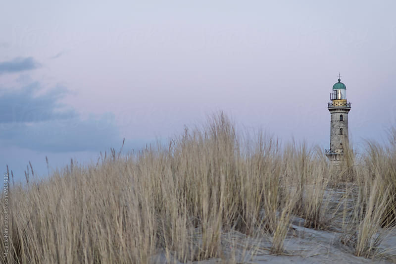 Lighthouse in Warnemuende behing dunes at dusk by Melanie Kintz for Stocksy United