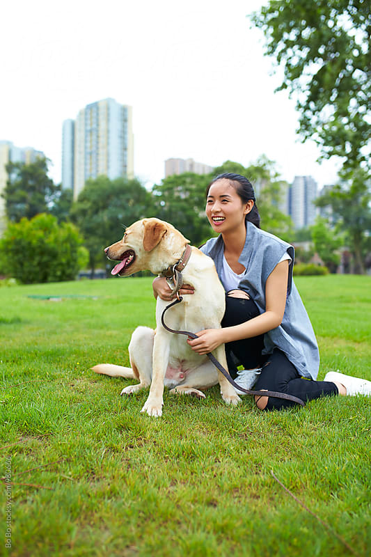 happy young asian woman outdoor with her dog by cuiyan Liu for Stocksy United