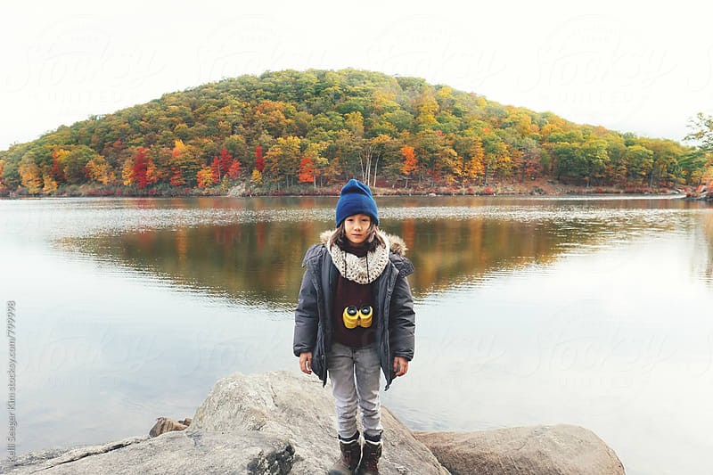 Young mixed race boy stands alone in front of lake by Kelli Seeger Kim for Stocksy United
