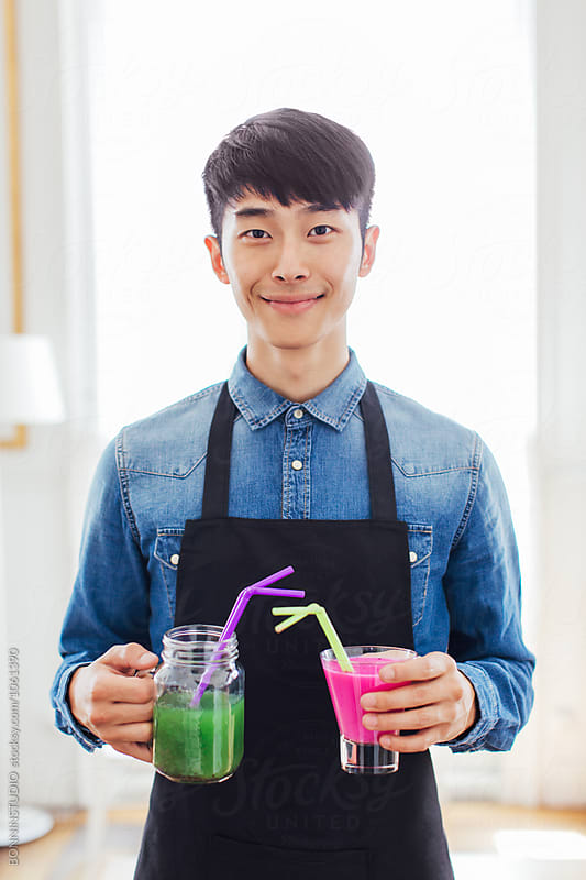 Portrait of an asian waiter serving colorful fresh smoothies in a restaurant.  by BONNINSTUDIO for Stocksy United