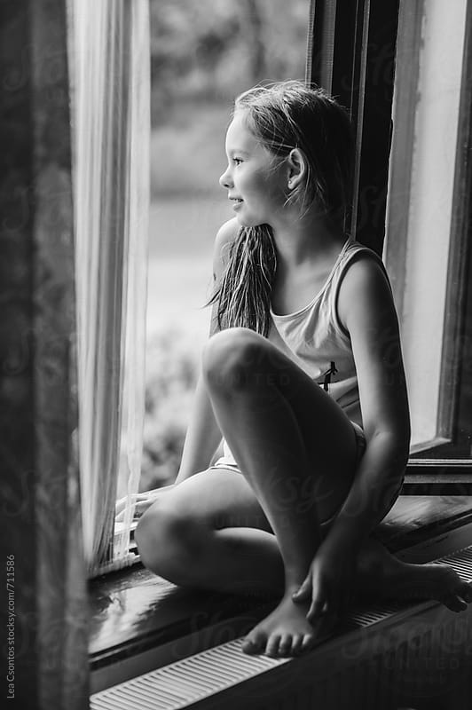 Girl sitting in a window looking out and enjoying the view by Lea Csontos for Stocksy United