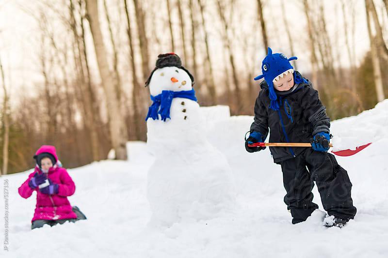Children Building a Snowman Outdoors in Winter by JP Danko for Stocksy United