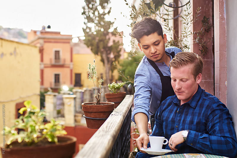 Waiter serving young man a cup of coffee by Per Swantesson for Stocksy United