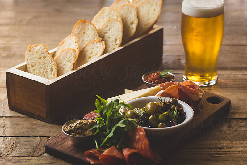 Charcuterie plate with bread and beer on a wooden table by Christian Tisdale for Stocksy United