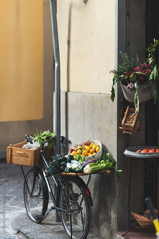 A bicycle parked outside a store loaded with veggies and fruits by Luca Pierro for Stocksy United