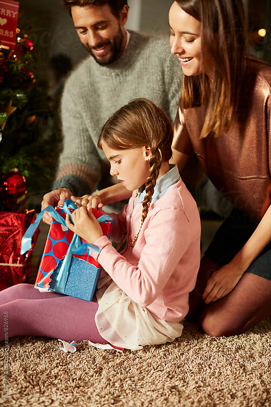 Parents Looking At Girl Opening Christmas Present At Home by ALTO IMAGES for Stocksy United
