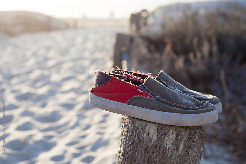Boy's slip on shoes left on a wood fence - path to the beach by Carolyn Lagattuta for Stocksy United