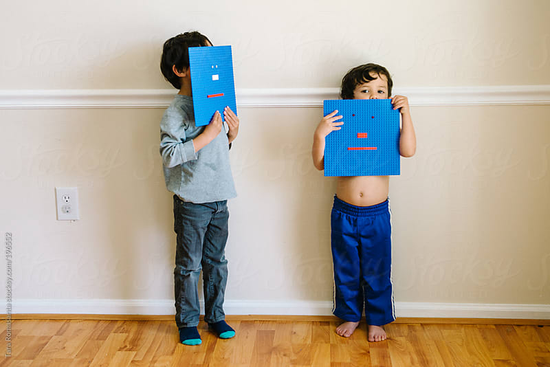 two little boys play behind building block toy faces by Tara Romasanta for Stocksy United