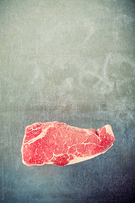 Food: Raw Steak on Metal Background by Sean Locke for Stocksy United