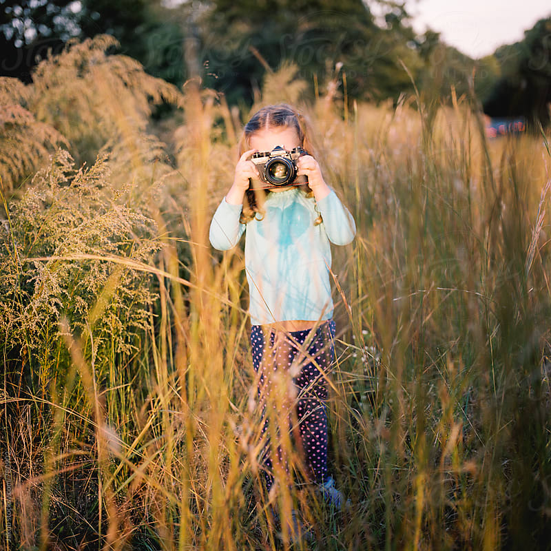 Young girl standing in a field with a camera by Jakob for Stocksy United