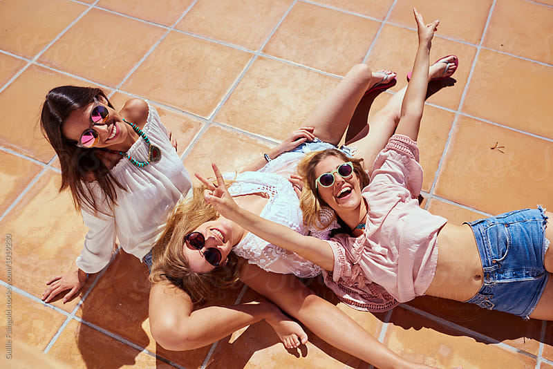 Cheerful girls on floor having fun in sunlight by Guille Faingold for Stocksy United
