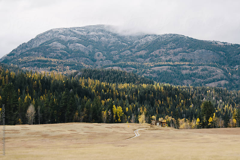 Homemade cabin in a rural mountain landscape by Justin Mullet for Stocksy United