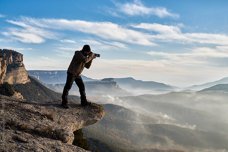 Professional photographer taking photo while standing on cliff by Guille Faingold for Stocksy United