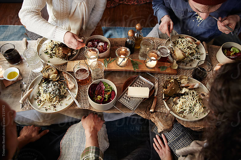 Group of friends having dinner together inside a cabin by Trinette Reed for Stocksy United