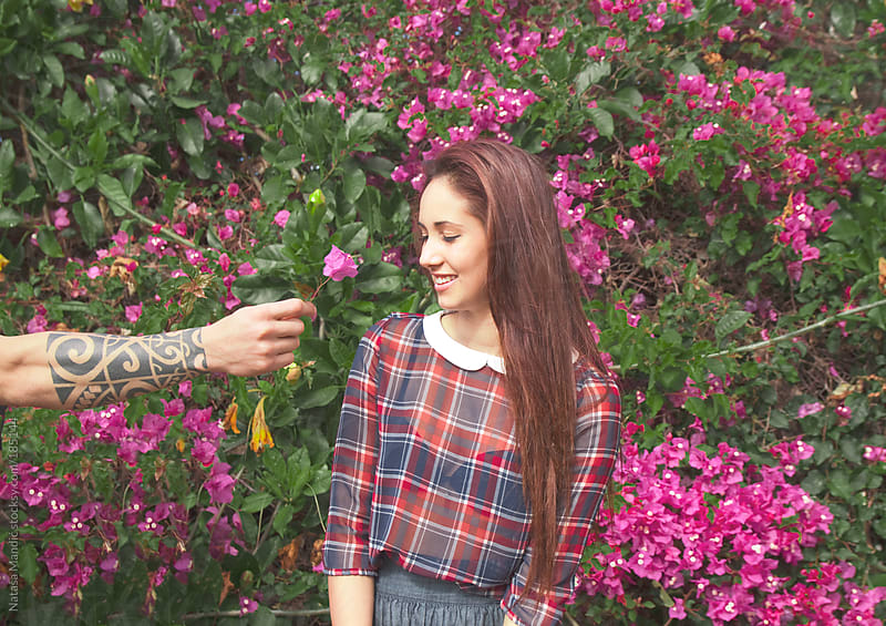 Young woman receiving a flower by Nataša Mandić for Stocksy United