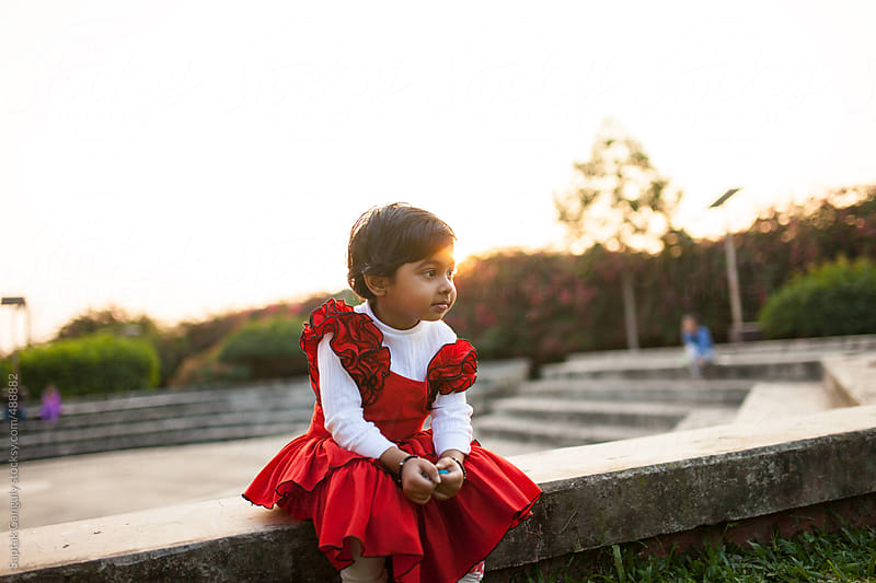Cute toddler sitting on the steps of an open air theater at sunset by Saptak Ganguly for Stocksy United