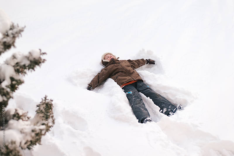 Young boy making a snow angel. by Lea Csontos for Stocksy United