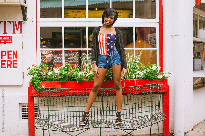 Black girl in Americana top standing on bench by Gabrielle Lutze for Stocksy United