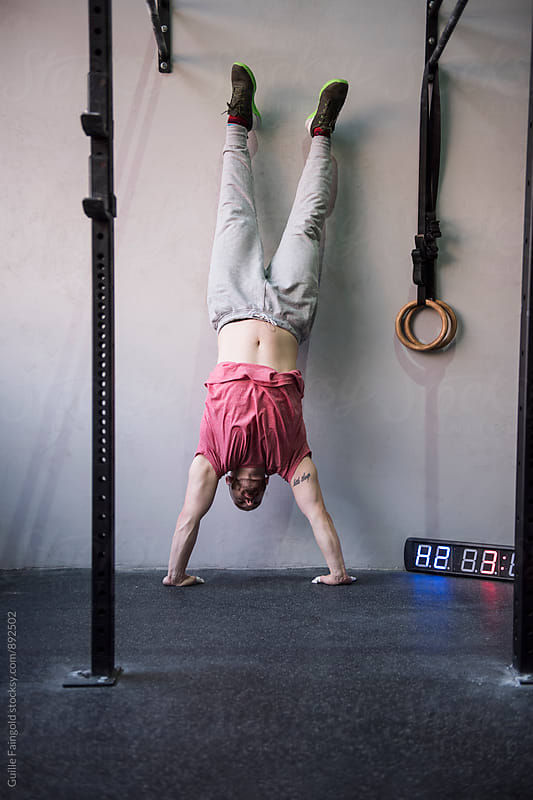 Man does handstand close to wall. by Guille Faingold for Stocksy United