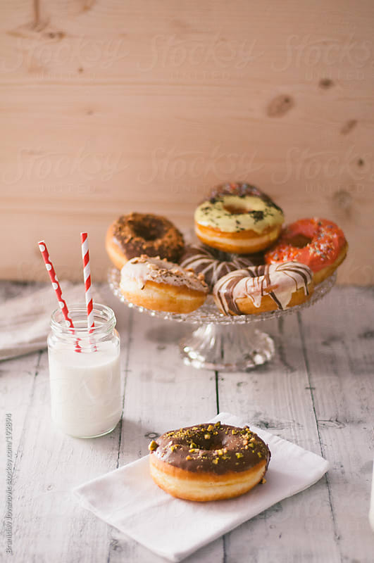 Donuts and milk on the wooden table by Brkati Krokodil for Stocksy United