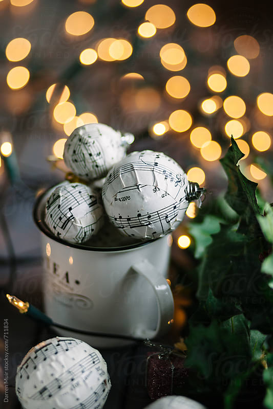 Handmade Christmas ornaments in an enamel mug with blurry christmas lights in the background. by Darren Muir for Stocksy United