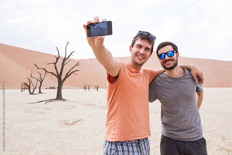 Two young happy friends taking a selfie picture in the arid desert of namibia by Alejandro Moreno de Carlos for Stocksy United