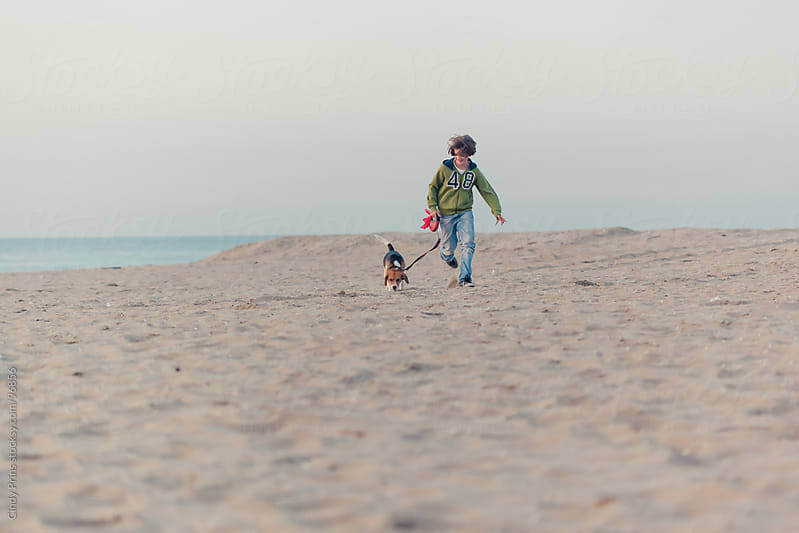 Boy running with a beagle dog on a leash on the beach by Cindy Prins for Stocksy United