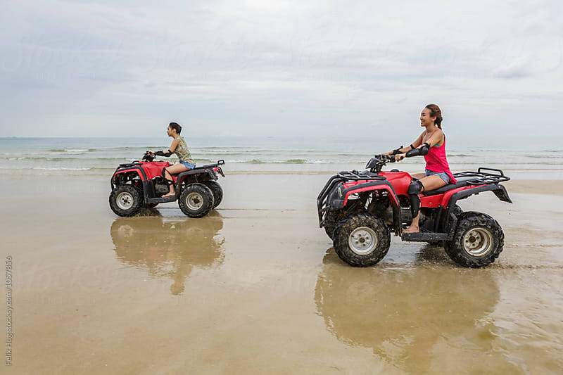 Two girls driving an ATV by Felix Hug for Stocksy United