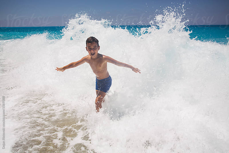 Boy enjoying playing in the sea. by Dejan Ristovski for Stocksy United