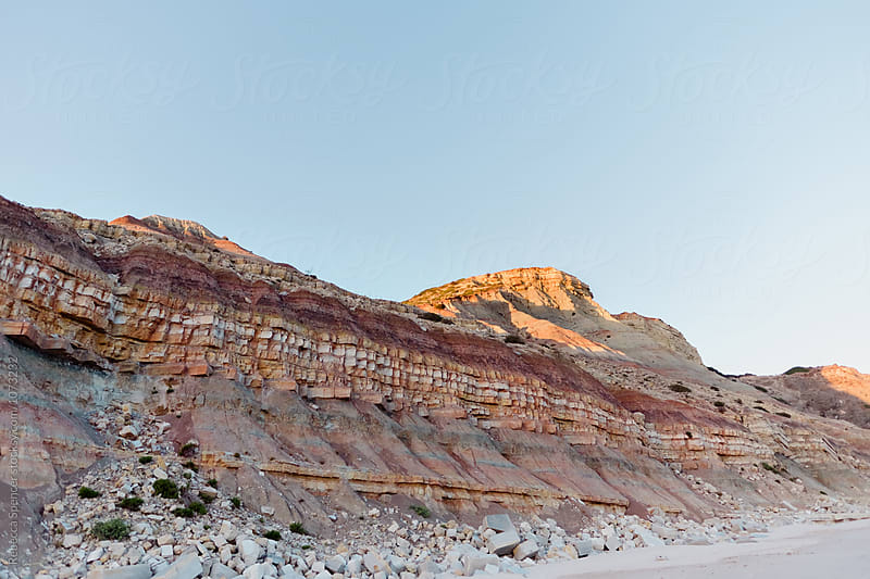 Colorful cliff face with fallen rocks by Rebecca Spencer for Stocksy United