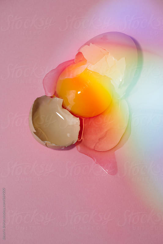 A broken egg in colorful light by Beatrix Boros for Stocksy United