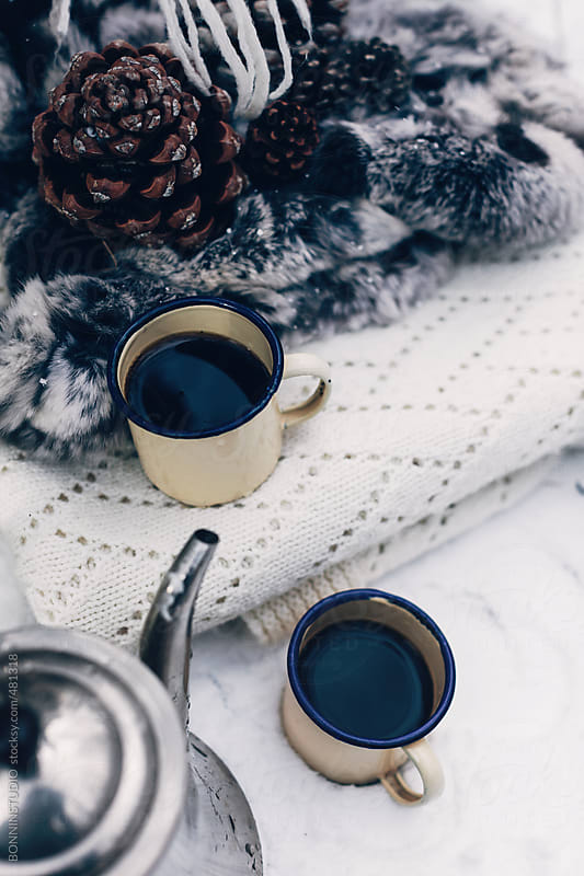 Still life of warm blankets and coffee cups on a snow covered grass. by BONNINSTUDIO for Stocksy United