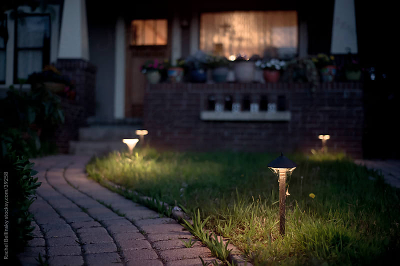 A lighted brick path leading to a house with glowing windows at night by Rachel Bellinsky for Stocksy United