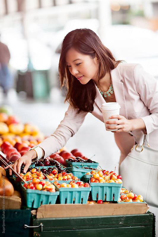 Beautiful Asian woman shopping for fruits at a farmers market by Suprijono Suharjoto for Stocksy United