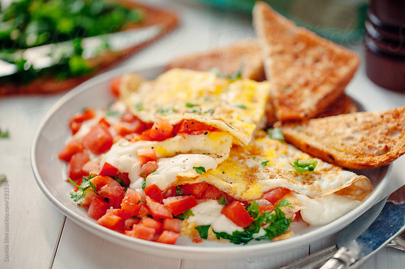 Omelette with fresh tomatoes and cheese by Davide Illini for Stocksy United