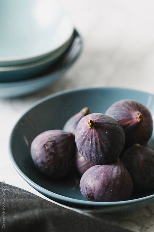 Ripe figs in a blue bowl. by Darren Muir for Stocksy United