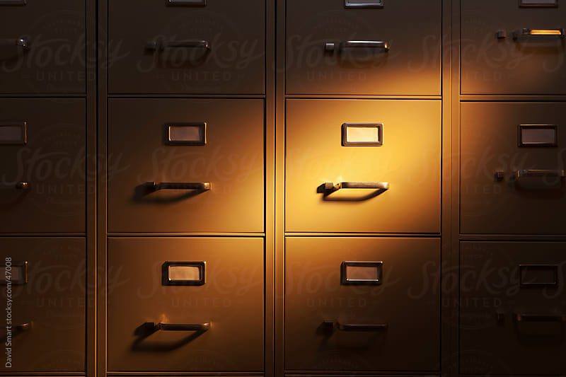 Spotlight shining on a wall of metal filing cabinets by David Smart for Stocksy United