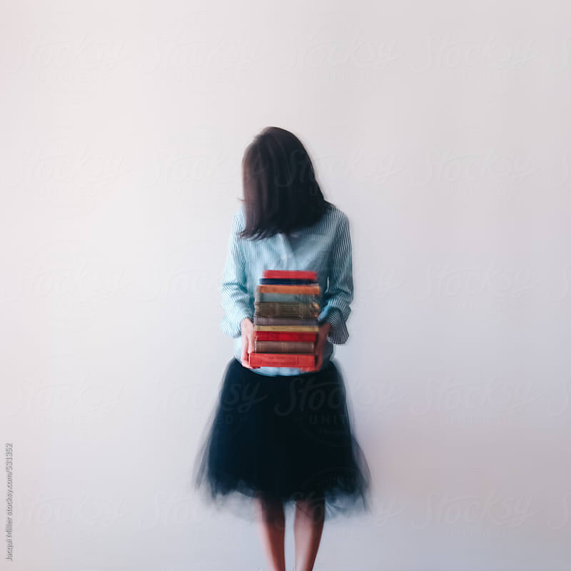 Movement image (intentionally blurred) of unrecognisable woman holding a stack of books by Jacqui Miller for Stocksy United