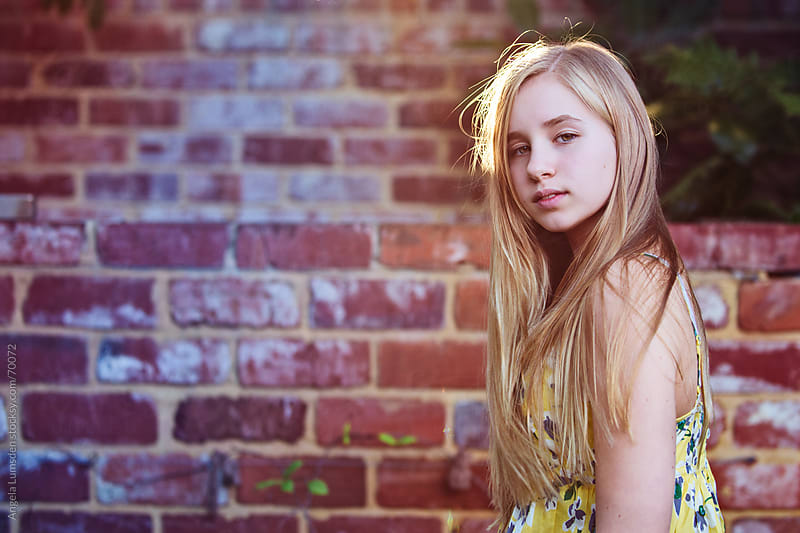 Girl with long blond hair in front of brick wall by Angela Lumsden for Stocksy United