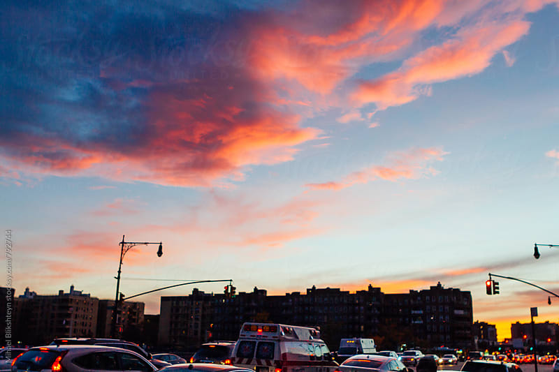 Evening skyline of buildings and cars  with a fiery sunset by Mihael Blikshteyn for Stocksy United