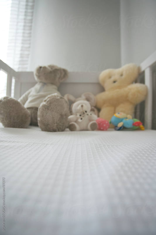 A cute crib of a baby with variety of teddies. by BONNINSTUDIO for Stocksy United