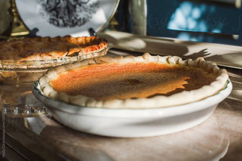 Homemade pumpkin and apple pies on a marble-topped sideboard. by Holly Clark for Stocksy United