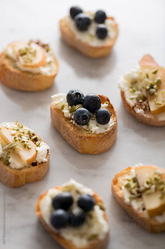 Crostini with Goat Cheese, Pear and Blueberry by Jeff Wasserman for Stocksy United