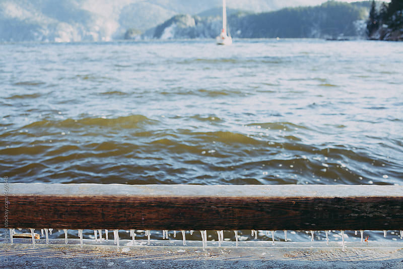 Tiny icicles hanging from the dock. by Cherish Bryck for Stocksy United