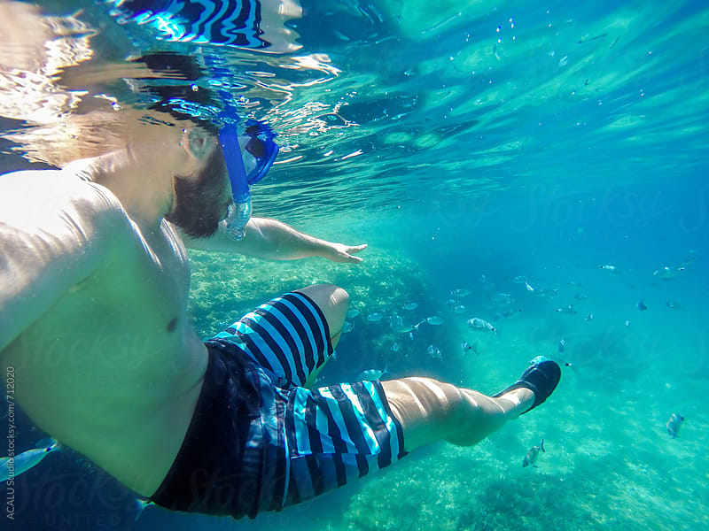 Young man snorkeling in crystal clear waters by ACALU Studio for Stocksy United