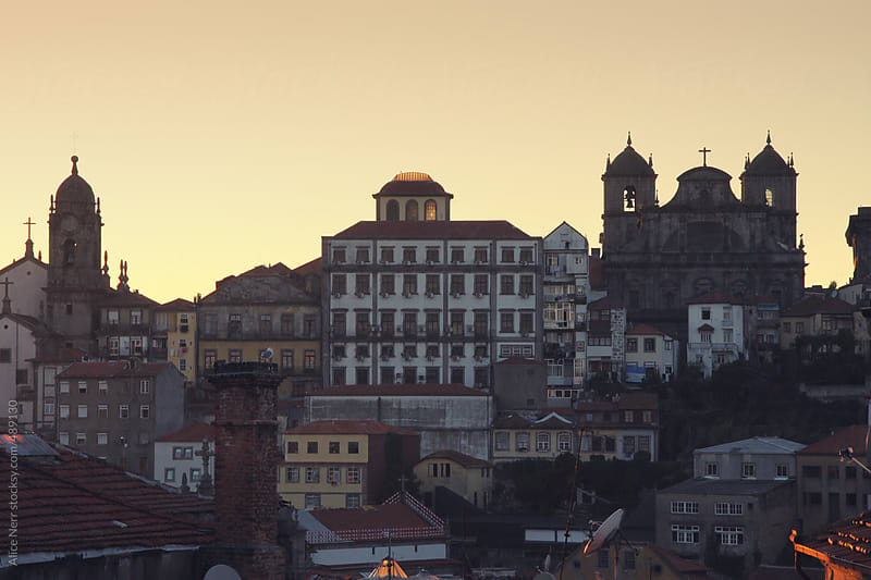Old Portuguese quarters featuring tower and church at the sunset by Alice Nerr for Stocksy United