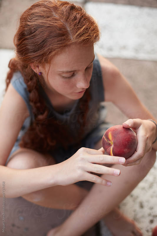 Young girl sitting on the ground with a peach by Miquel Llonch for Stocksy United