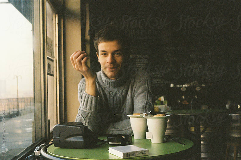 Film photography of a young man in the cafe by the window by Nabi Tang for Stocksy United
